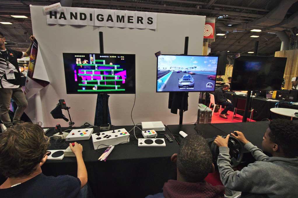 Photo : Des joueurs essayent les manettes adaptées mises à disposition par Hitclick sur le stand Handigameurs de la Paris Games Week